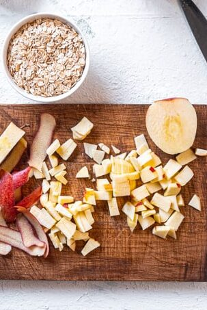 A wooden cutting board with diced apples, apple peels, and half an apple. To the top left is a small white bowl with uncooked oats