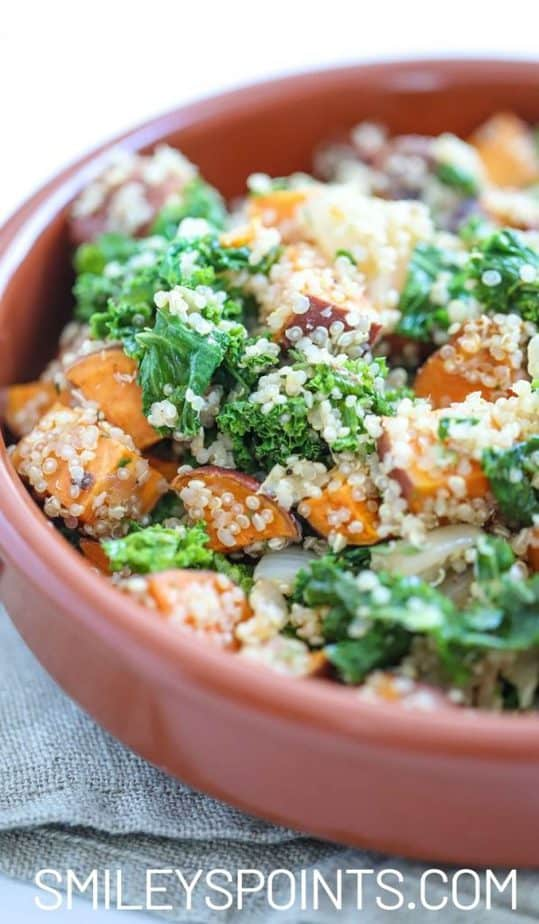 Orange bowl with cubes of sweet potatoes and kale covered in quinoa. Bowl is on a grey tablecloth.