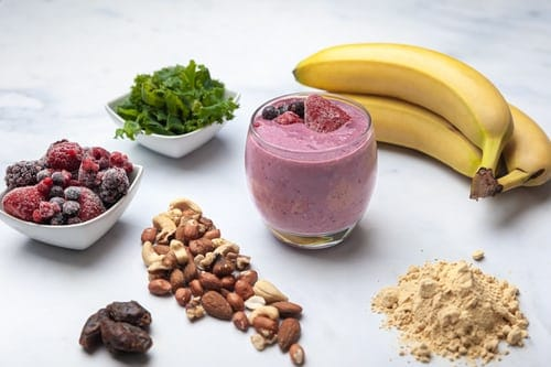 On a white table there's a small glass with a purple smoothie in it. There are a few pieces of fruit on the top of the glass. On the table, in a circle around the glass are bananas, greens, berries, nuts and protein powder.