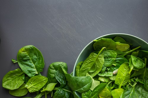 On a grey table, there's a metal bowl filled with spinach leaves, with leaves on the table to the left of the bowl.