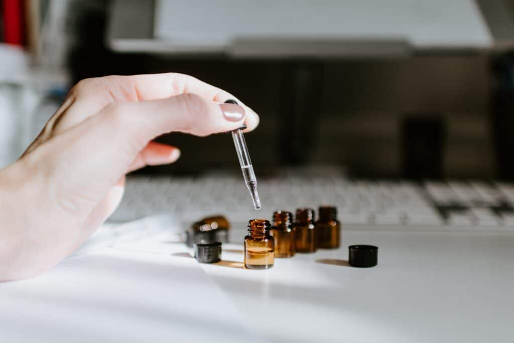 Essential oils. A hand dropping oil into little jars