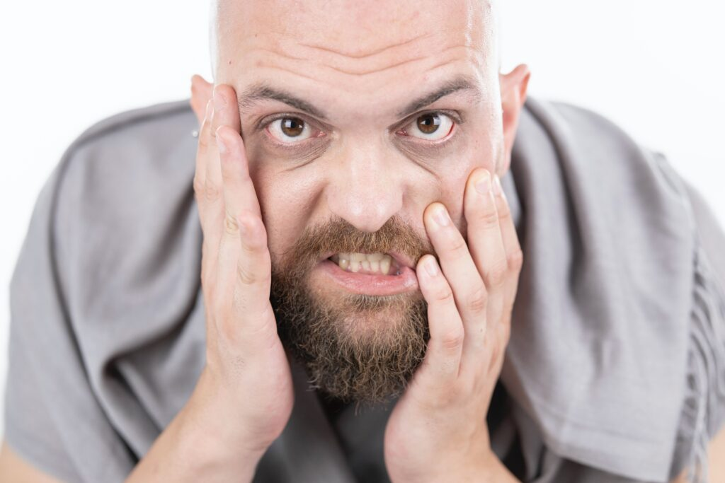TMJ Don't clench your teeth. Man with a beard with his hands on his face teeth clenched.