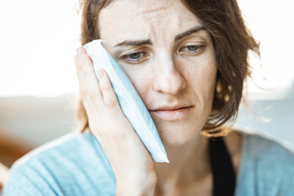 TMJ pain. Picture of a woman holding an ice pack to her jaw.