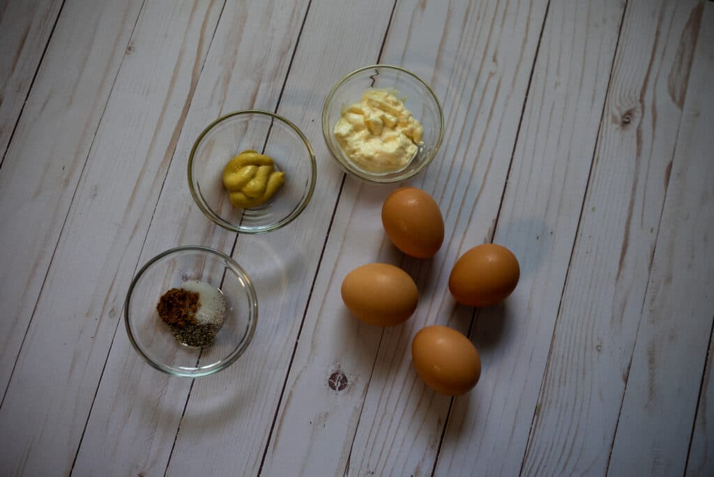 Ingredients for curried deviled eggs. Brown eggs and ingredients in clear bowl on a wood table