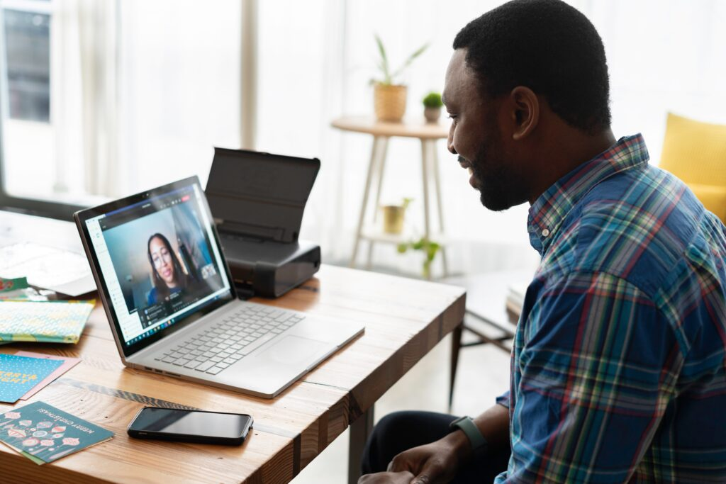 Man looking at a computer screen with a woman on it. Online coaching.