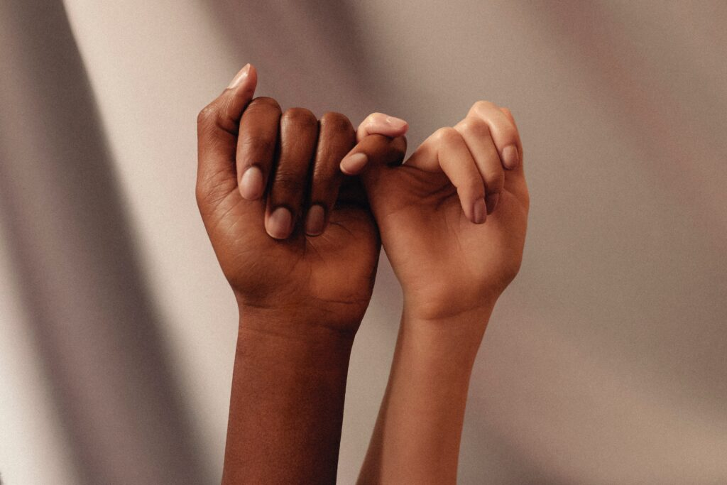 Be there for each other. two hands clasping with pinky fingers