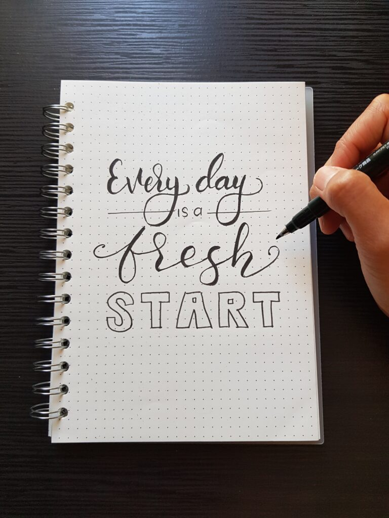 Every day is a fresh start written on a notebook in cursive.